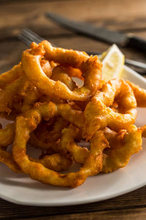 calamares: Traditional spanish fried squid on a wooden table.