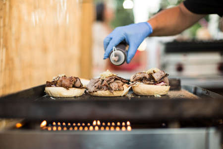 anonymous people: Crop faceless shot of person in gloves pouring sauce on burgers.