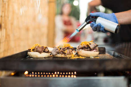 Chef in gloves using gas torch and burning cheese while making burgers.