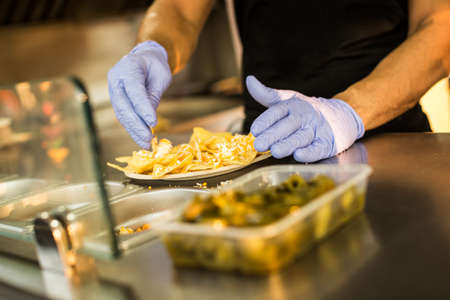 Crop faceless shot of person in gloves cooking nachos in food truck.