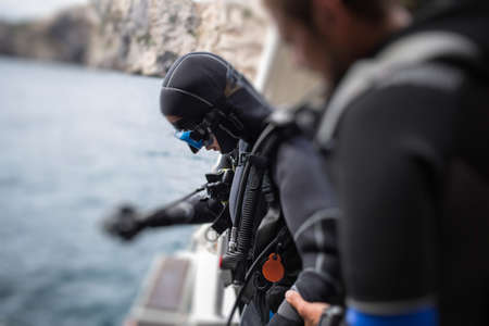 Side view of unrecognizable scuba diver preparing to dip on a river. Stock Photo
