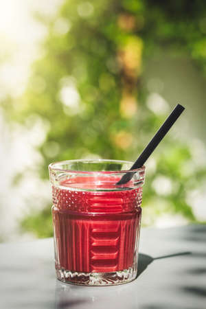 Red smoothie juice glass  with copy space in a sunny outdoors.