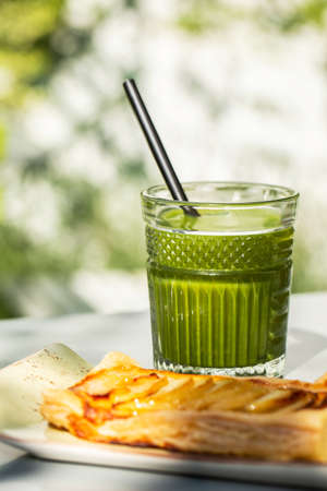 Green detox juice glass with an apple pie in a sunny outdoors