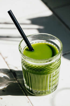 Green detox juice glass in a white tile table