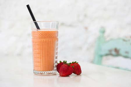 Fresh strawberry smoothie on a white table, copy space. Archivio Fotografico