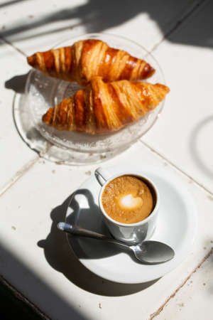 Hot coffee and croissant breakfast in a sunny morning, natural light. Archivio Fotografico
