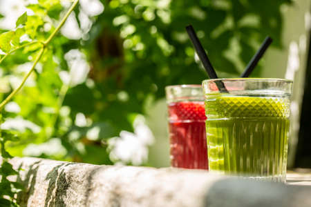Red and green detox juice glass  with copy space in a sunny outdoors