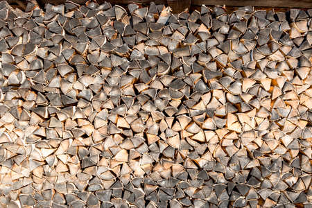 The pile of dry wood harvested for heating in the farmhouse in winter. Laid in neat rows in stock.
