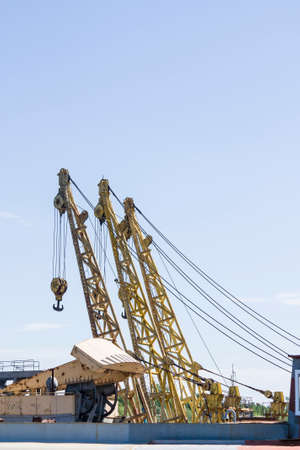 Large port cranes against a blue sky. Close-up of the construction elements of the crane.