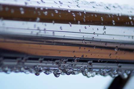 Tubos de acero cromado con gotas de agua en el puerto fluvial después de la lluvia. Foto de archivo