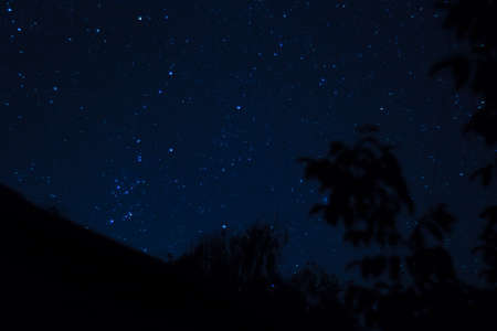 Long exposure night photo. A lot of stars with roof on foreground. Far from the city.