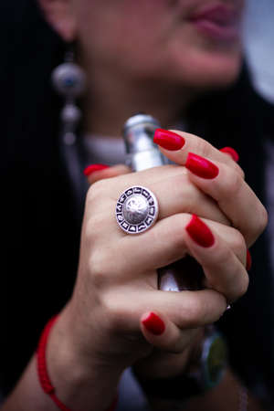 Caucasian woman with red nails manicure and antique ring on finger holds small vape. Smoking alternative vay. Life without cigarettes. Woman-vaper. Small e-cigarette.