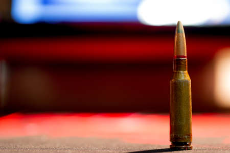 Rifle AK-47 ammo bullet close-up on blurred background. Armor piercing cartridge.