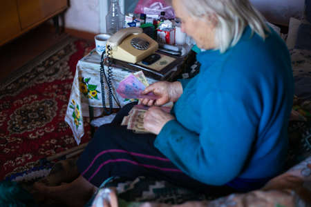 Ukraine, Kyiv, December 12 2018. Old poor gray hair woman holds ukrainian paper money in her hands. Woman is sad. Poor life in village. Old age not good. Low-light photo. Editorial Use Only. Banco de Imagens - 115828910