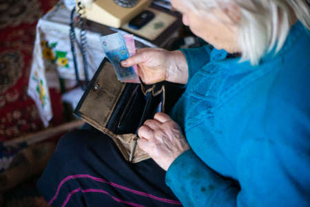 Old poor gray hair woman putting paper Ukrainian money in her vintage leather wallet by her hands. Woman is sad. Poor life in village. Old age not good. Low-light photo.