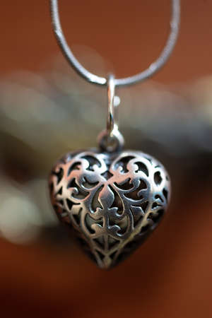 Close up photo of female neck silver pendand on blurred background. A handwork sterling silver pendant look as heart. Macrophoto with blurred background.