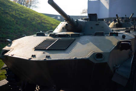 Parts of the hull of the armored infantry vehicle. In front and back of vehicle stays many different armored military vehicles. Military equipment outdoor open air museum.