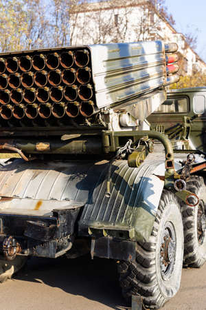 Camouflage military truck with rocket launcher. Outdoor military vehicles museum. Armor is damaged at the battlefield. Missile firing system on military armored truck close up view. Rocket launcher.