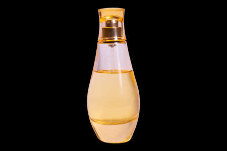 Warm yellow colour glass perfume bottle isolater on black background.
