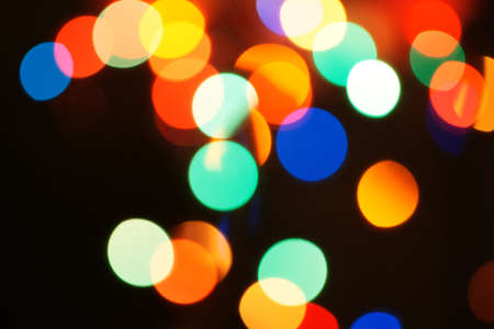 Multi-color holiday garland. Garland is blurred. Many colorful round lights. Fully defocused photo. Blurred background and foreground. Holiday mood. New Year and Christmas is coming. Stock Photo