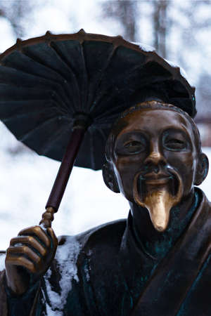 Bronze monument of a chinese old man with umbrella in winter snow park. Closeup with blurred background.