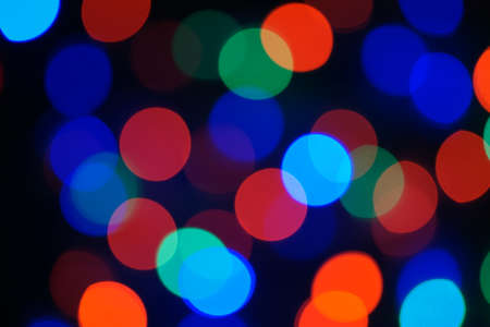 Multi-color blue holiday garland. Garland is blurred. Many big colorful round lights. Fully defocused photo. Blurred background and foreground. Holiday mood. New Year and Christmas is coming.