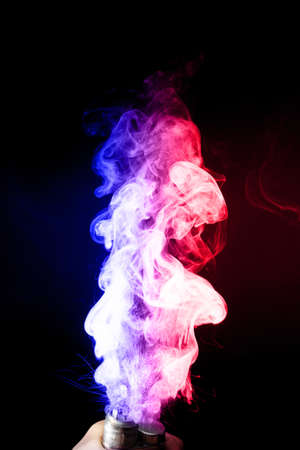 Male hand holds vape. Vape clouds splash from vape coil on black background. Fog is dual color — blue and red. Stock isolated dual colour smoke with spray boiling glycerine. Stockfoto - 118920375
