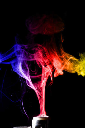 Color clouds splash glicerine on vape spiral. Many colour of fog with visible tracers. Vape culture and no smoking propaganda. Foto de archivo