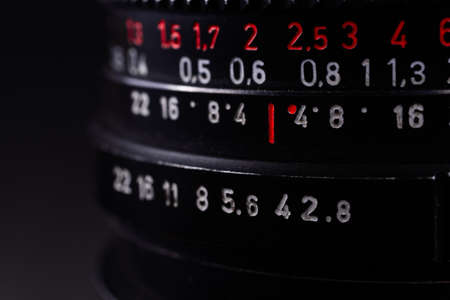 Vintage lens scale signs closeup. Stock photo with blurred gray background.