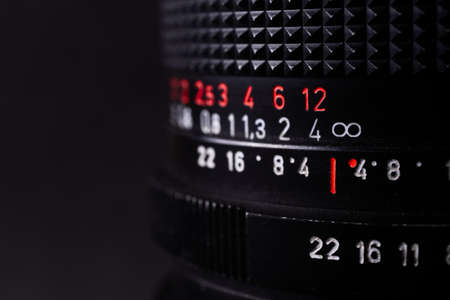 Vintage lens scales symbols closeup. Stock photo with blurred gray background. Aperture symbols and focusing distance signs on lens.