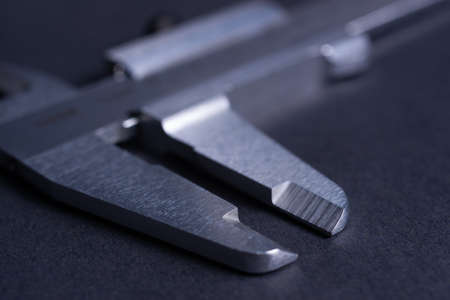 Vintage steel caliper tool closeup. Caliper tips in focus. Tool in very good condition. Scale in metric units, milimeter step. Stock photo on blurred gray background.