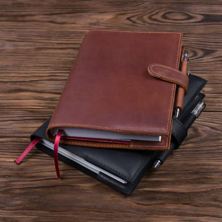 Brown and black handmade leather notebook covers with notebook and pen inside on wooden background. Stock photo of luxury business accessories.