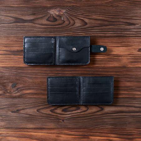 Zwei schwarze handgemachte Ledergeldbörsen auf strukturiertem Holzhintergrund. Ansicht von oben nach unten. Geldbörse stockfoto. Standard-Bild