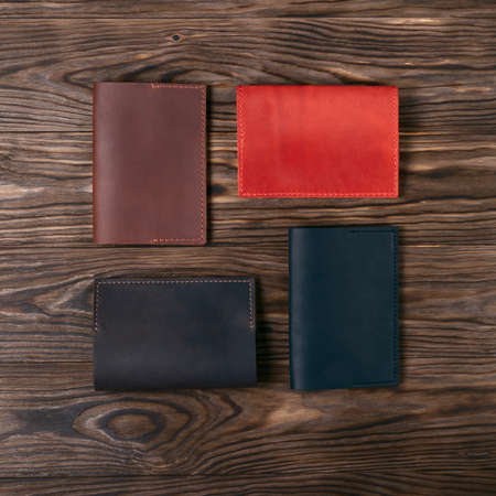 Four handmade leather passport covers on wooden textured background. Black, red, ginger and brown covers. Up to down view. Stock photo of luxury accessories.