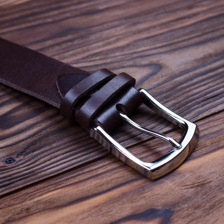 Brown handmade belt buckle lies on textured wooden background closeup. Side view. Stock photo of businessman accessories.