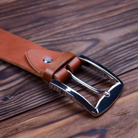 Hue ginger color handmade belt buckle lies on textured wooden background closeup. Side view. Stock photo of businessman accessories.