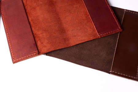 Two handmade leather passport covers isolated on white background. Closeup view. Covers are red, brown and open. 写真素材