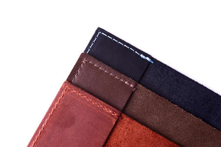 Three handmade leather passport covers stack isolated on white background. Closeup view. Covers are dark blue, red, brown and opened.