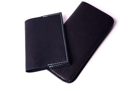 Black handmade leather man wallet and passport cover isolated on white background. Purse and cover are closed. Stock photo of luxury businessman accessories.