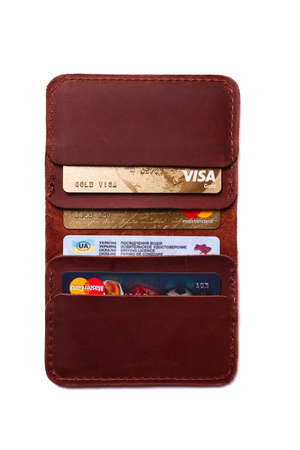 24.01.2019 Ukraine, Kyiv. Handmade red color leather cardholder isolated on white background closeup. A lot of plastic cards in pockets. Editorial use only. Editorial