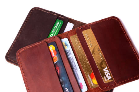 24.01.2019 Ukraine, Kyiv. A part of handmade red and brown color leather cardholders isolated on white background closeup. A lot of plastic cards in pockets. Editorial use only. Editorial