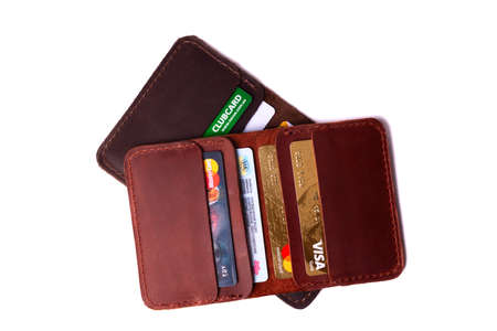 24.01.2019 Ukraine, Kyiv. Handmade red and brown color leather cardholders isolated on white background closeup. A lot of plastic cards in pockets. Editorial use only. Editorial