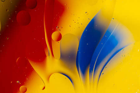 Abstract oil spots in motion on water on blurred yellow background. Red and blue spots on blurred background. Photo with small depth of field. 写真素材