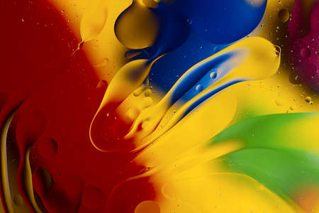 Abstract oil spots in motion on water on blurred yellow background. Red, green, purplee and blue spots on blurred background. Photo with small depth of field. 写真素材