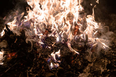 A low light underexposed photo of burning fire. Many sparks and flames. Burning books and wood.