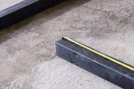Measuring tape on black square huge pipe on concrete floor.