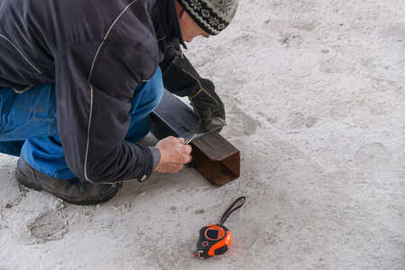 A builder draws on a square metal pipe using a locksmith on the concrete floor.