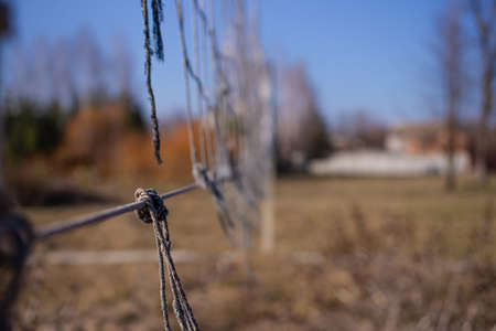 Torn volleyball net in an abandoned stadium. It`s autumn time outside. Post apocalyptic concept. Standard-Bild