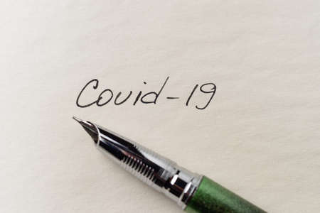 Covid-19 inscription on a blank empty sheet of paper in a notebook. Nearby lies a fountain pen. A lot of space for inscriptions and copyspace. The virus is dangerous. Blank for inscriptions. Template for article or cover. Stock fotó