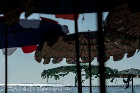 recourse: ocean view through umbrellas